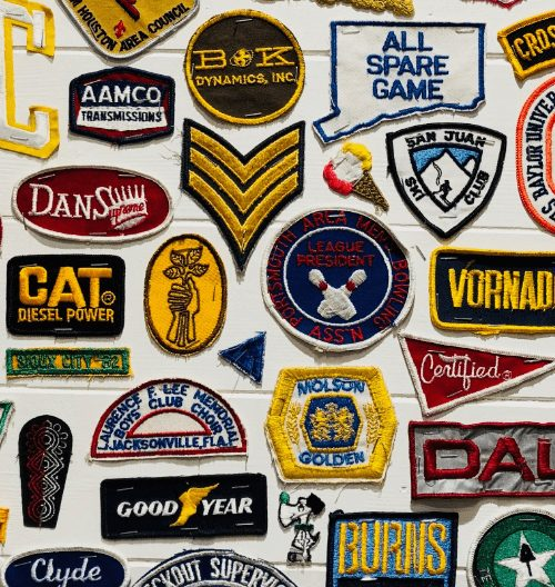 Numerous embroidery logos against a wall